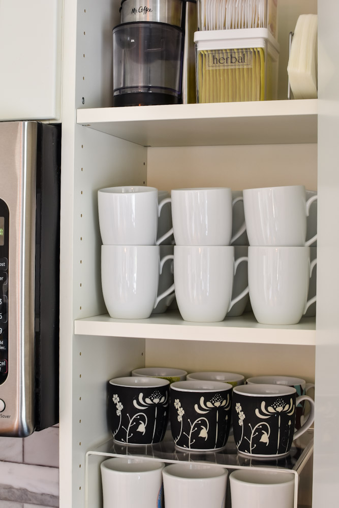 white mugs and black mugs in a cabinet