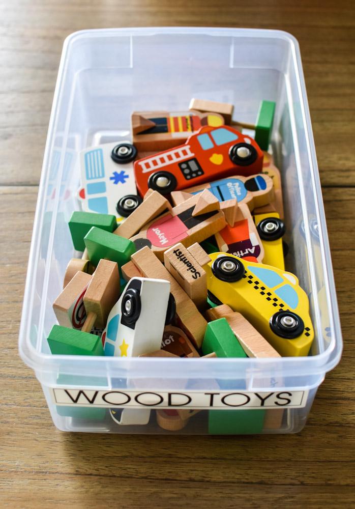 wood toys in a clear storage bin