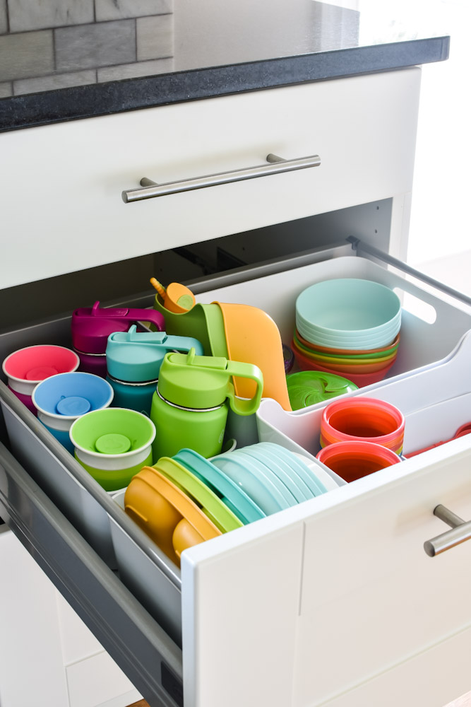 organized kitchen drawer of kid cups and plates