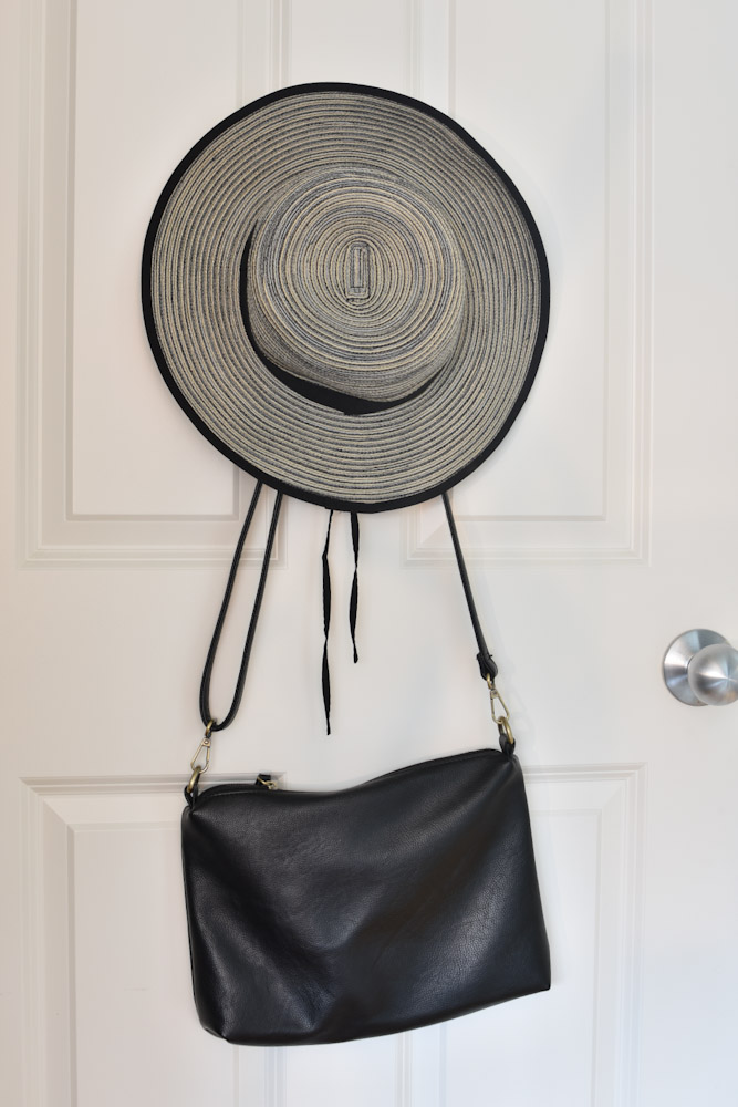 purse and hat hung on back of closet door